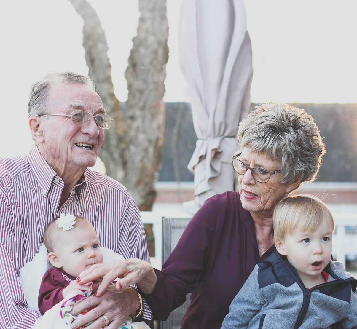 Grandparents smiling happily with their granddaughter and grandson